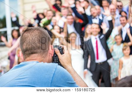 Wedding Photographer In Action, Taking A Picture Of Group Of Guests