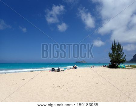 HONOLULU HAWAII - APRIL 25: People hang out on Waimanalo Beach as gentle wave lap on on shore looking towards Rabbit island and Rock island on a nice day Oahu Hawaii. April 25 2016.