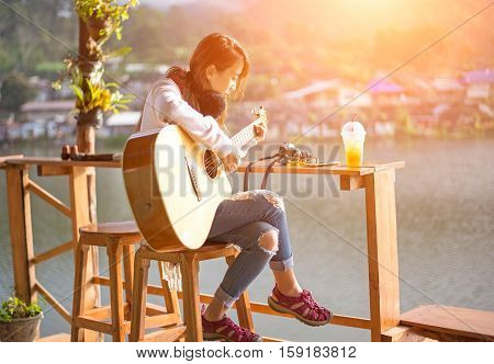 Young women playing acoustic guitar, Soft focus