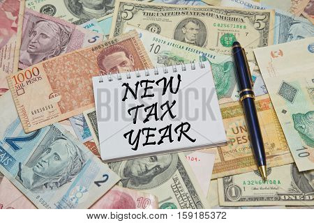 Notebook with text NEW TAX YEAR on dollar background