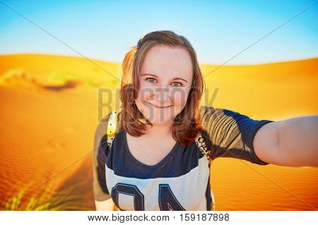 Happy smiling tourist taking selfie with sand dunes in Sahara desert at Erg Chebby Merzouga Morocco