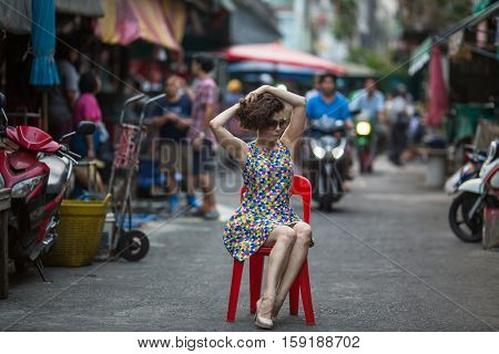 Young asian woman is sitting on a chair in the middle of a bustling street.