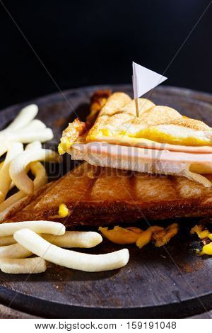 Sandwish ham cheese with frenchfries on wood plate and black background