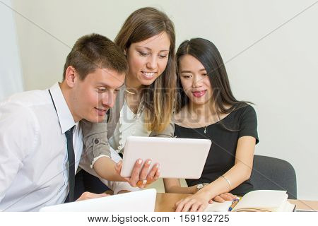 Multicultural Team Looking At A Tablet