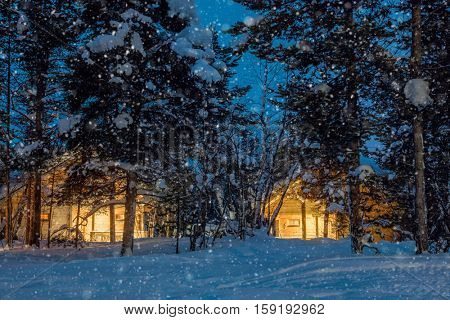 Winter snowfall night, small wooden houses with warm light, a lot of snow, quiet winter landscape