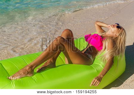 Sexy blonde with long hair resting on an inflatable banana on a tropical beach. Summer vacation concept.