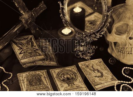 Still life with the Tarot cards, mirror, candles and skull in sepia grunge style. Halloween concept, black magic ritual or spell with occult and esoteric symbols. Vintage objects on witch table