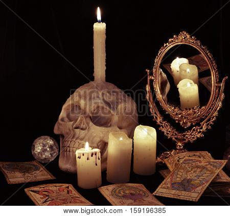 Still life with skull, mirror and the tarot cards in candle light. Halloween concept, black magic ritual or spell with occult and esoteric symbols, divination rite. Vintage objects on witch table