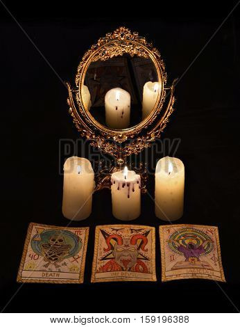 Vertical vintage still life with divination rite objects - mirror, candles and the tarot cards. Halloween concept, black magic ritual or spell with occult and esoteric symbols