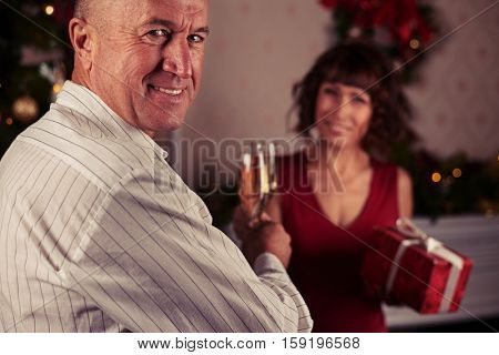Close-up rack shot of smiling senior man toasting glasses while exchanging gifts, isolated in the romantic atmosphere. Woman holding a present box in hand