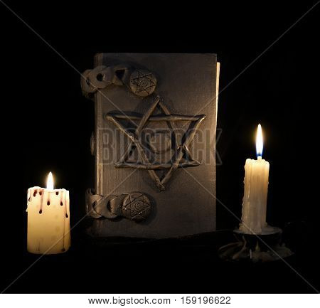 Black magic book with pentagram in the darkness. Halloween concept, black magic ritual or spell with occult and esoteric symbols, divination rite. Vintage objects on table