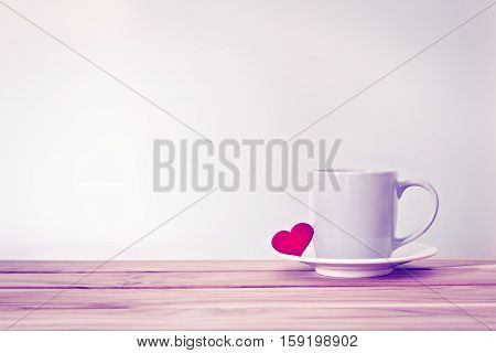Coffee cup mug with red heart shape on wooden table Romance and love valentines day background concept . Vintage retro color style