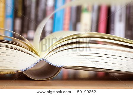 Close up opened book page with blurry bookshelf background for education and publication concept extremely shallow DOF
