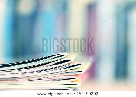 Close up edge of colorful magazine stacking with blurry bookshelf background for publication and publishing concept extremely shallow DOF