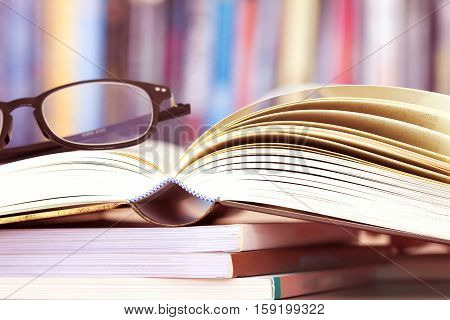 Close up opened book page and reading eyeglasses with blurry bookshelf background for education and publication concept extremely shallow DOF