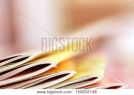 Close up edge of colorful magazine stacking with blurry bookshelf background for bublication and publishing concept extremely DOF