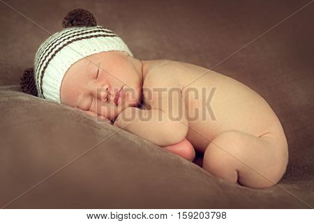 Newborn baby boy sleeping peacefully in the fetal position on a brown background with the beanie with ears in the image of teddies