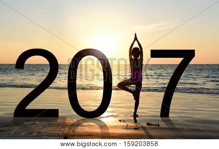Happy new year card 2017. Silhouette of A girl doing Yoga vrikshasana tree pose on tropical beach with sunset sky background watching the sunset standing as a part of the Number 2017 sign.