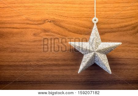 Silver glittering star ornament on wooden background leaving copyspace on the left