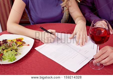Close-up of female hands signing contract at the dining table