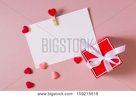 Valentine day composition: red gift box with bow stationery / photo template with clamp and small hearts on light pink background. Top view.