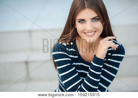 Spring portrait of a happy brunette woman with long straight hair and gray-green eyes,light makeup,nice smile,white straight teeth,dressed in a dark pullover with white stripes posing on a city street,on a white background