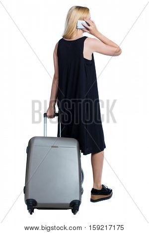 Back view of woman with suitcase looking up. Standing young girl. Rear view people collection. Isolated over white background. Long-haired blonde in black dress talking on phone and holding a suitcase
