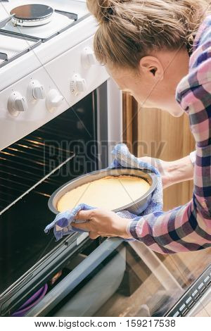 Girl Using Dishcloth For Taking Cheesecake Out Of Oven