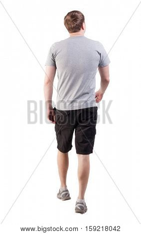 Back view of walking handsome man in shorts and sneakers.  backside view of person.  Isolated over white background. broad-shouldered guy is looking forward to the left