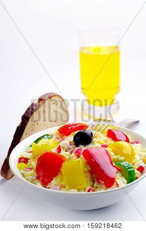 Salad with crab sticks rice vegetables and a glass of juice
