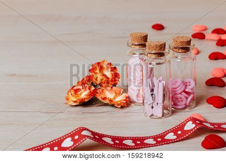 Valentine or holiday composition: close up of bright small hearts spring flowers glass bottles with clothespins and buttons and red ribbon with pattern on wooden background. Copy space for text.