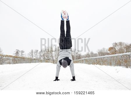 fitness, sport, training, people and exercising concept - young man on doing handstand outdoors in winter