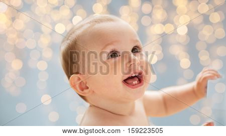 childhood, babyhood, emotions and people concept - happy little baby boy or girl looking up over holidays lights background