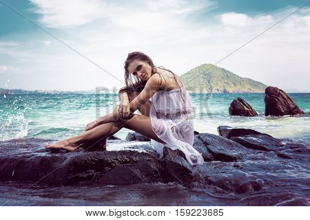 Sensual brunette woman in white dress with wet hair looking at the camera while sitting on the rock over beautiful sea and tropical island background