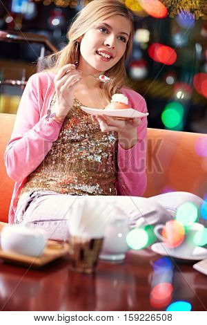 Beautiful blond girl eating dessert in cafe