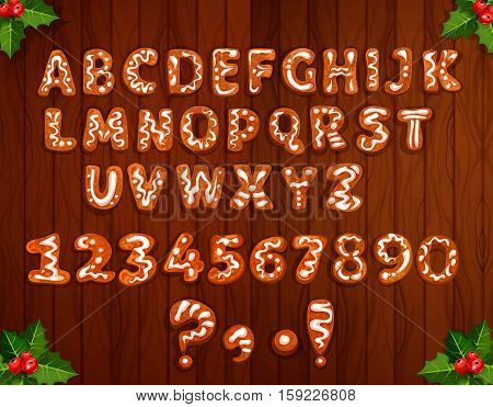 Letter and number font made up of Christmas gingerbread on wooden background, decorated by holly berry branches. Christmas gingerbread cookie alphabet for winter holidays theme design