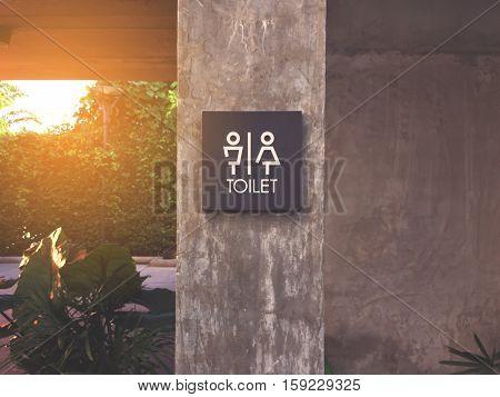Unisex restroom or toilet label on concrete post.