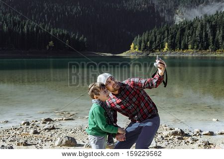 Handsome Traveler With Son Taking Photo At The Black Lake, Montenegro