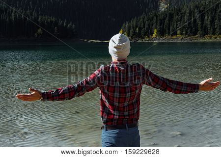 Hipster Traveler Raised Hands Against Black Lake, Durmitor National Park, Zabljak, Montenegro