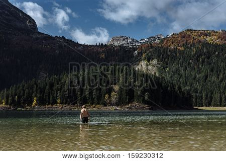 Hardening In Cold Water. Man Bathes In The Lake Autumn In Montenegro, Durmitor Park
