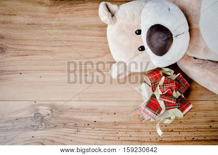 Little beautiful gift box with teddy bear on wood background vintage tone and soft focus concept of chritmas and new year day