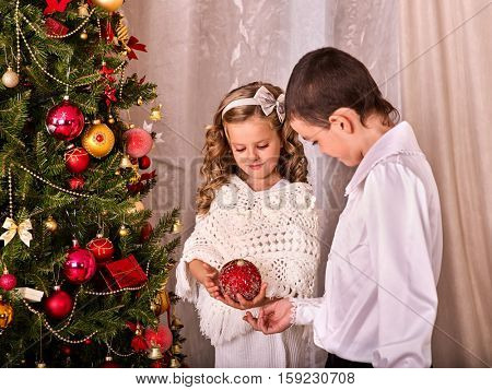 Children receiving gifts under Christmas tree. Brother and sister decorating a Christmas tree. Happy Family is preparing to celebrate Christmas.