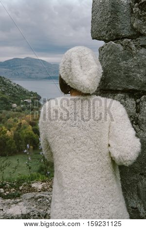 Hipster Woman Wearing Beige Sweater, Hat And Jeans Posing Against Stone Wall, Swag Street Style, Aut