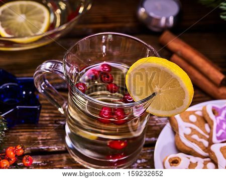 Top view of christmas glass latte mug and Christmas multicolored cookies on plate with fir branches. Mag decoration lemon slice and cinnamon sticks.