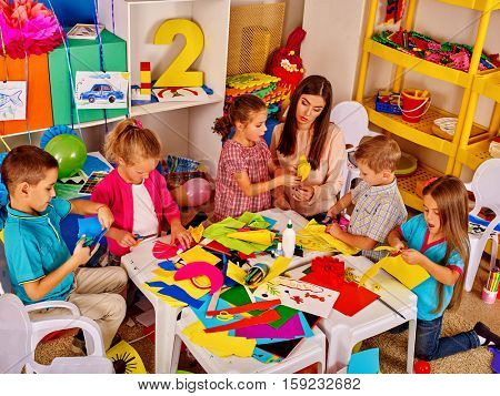 Large group of children with the teacher in a kindergarten. Children create crafts out of colored paper.