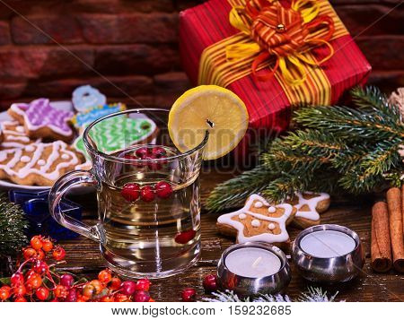 Warming drink decorate slice lemon and gift box. Warming grog with wine and cookie in form of star on brick wall.