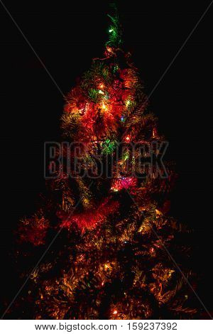 Blurred dark Christmas tree lights on black background