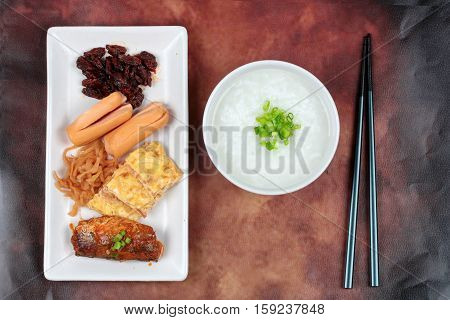 Rice gruel served with side dish as sausage spicy clams ,sweet radish omelet and spicy caned mackerel.