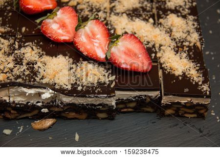 Slices of Chocolate Nut Brownies on top fresh strawberry