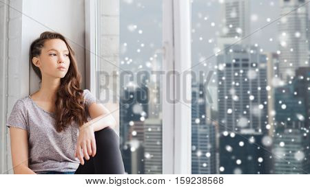 people, winter, christmas and teens concept - sad unhappy pretty teenage girl looking through window over snow